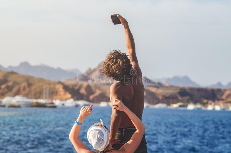 Sharm el-Sheikh, Egitto 8 maggio 2019: Tipo riccio scuro con una ragazza bianca prendere un selfie su uno smartphone sui preceden fotografie stock libere da diritti