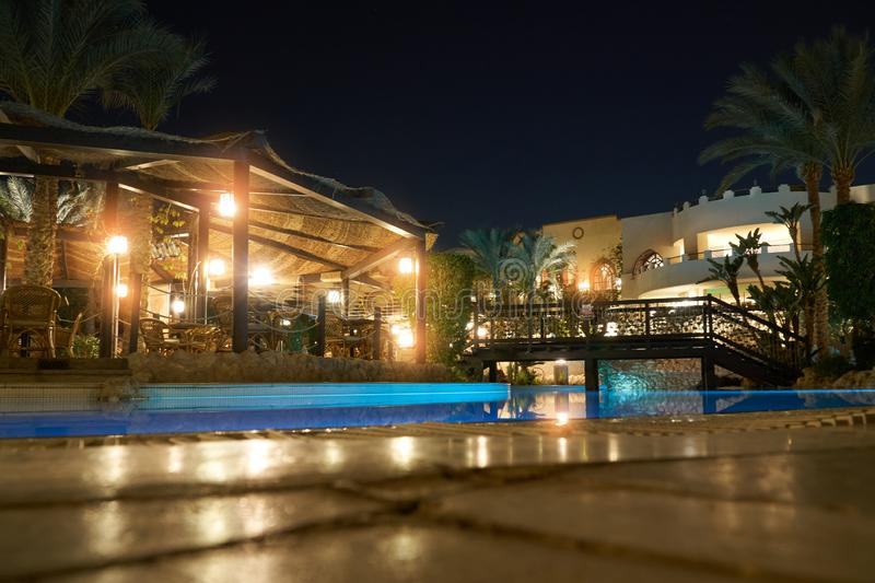 Sharm El Sheikh, Egypt - February 9, 2019: Night five-star The Grand Hotel with light palms and swimming pool on terrace royalty free stock photo