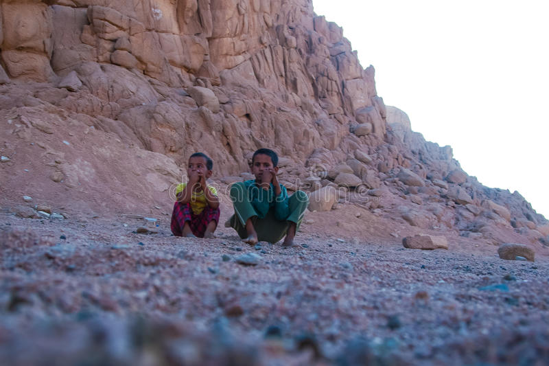 SHARM EL SHEIKH, EGYPT - JULY 9, 2009. Two children are sitting in the desert, and looking into the distance royalty free stock image