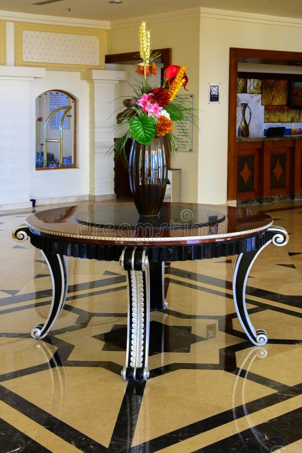 Sharm el-Sheikh, Egypt - March 14, 2018. The interior of the hotel lobby with reception, marble floor, showcases, a beautiful ston. E table with a vase of stock photography