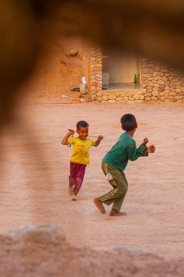 SHARM EL SHEIKH EGYPTEN - JULI 9, 2009 Två lyckliga barn som spelar i öknen royaltyfri fotografi