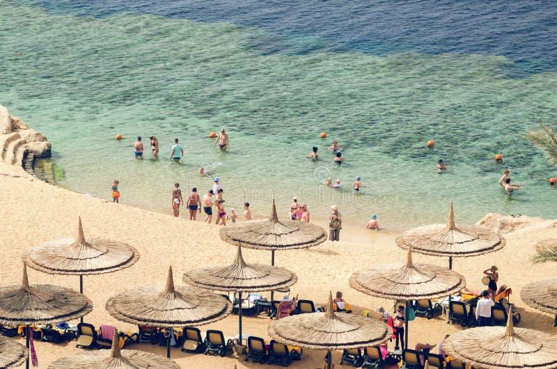 Sharm el Sheikh Egypten Maj 07, 2019: folket solbadar på soldagdrivare under paraplyer på stranden och badar i havet i Egypten royaltyfria foton