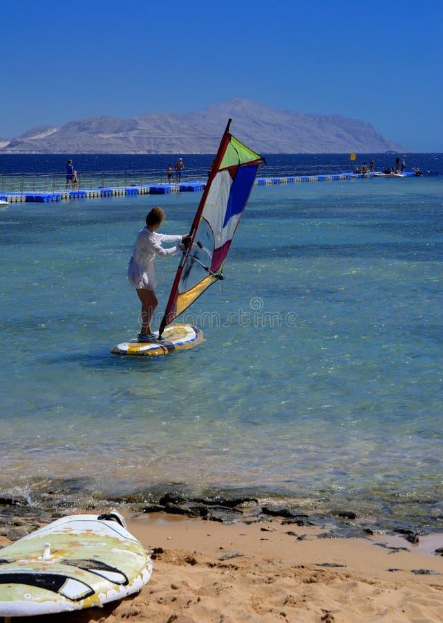 Sharm el-Sheikh Egypten - mars 14, 2018 En flicka kör ett bräde med en segla på masten tack vare böjelsen och vänden av masten royaltyfri fotografi
