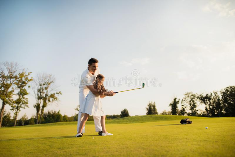 A sharp blow to the ball with a golf club. the girl made her first hit in golf royalty free stock photography