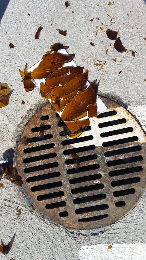 Sharp broken bottle glass by rusty storm drain in parking lot royalty free stock image