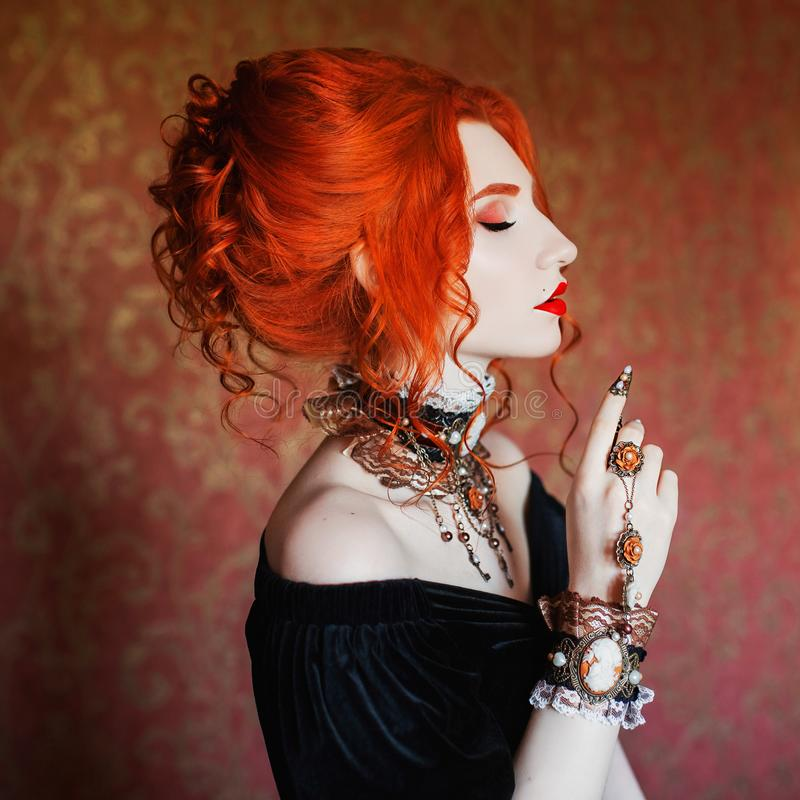 Sharp claws. Dark halloween attire. Goth woman is vampire with pale skin and red hair in black dress and necklace on neck. stock photography