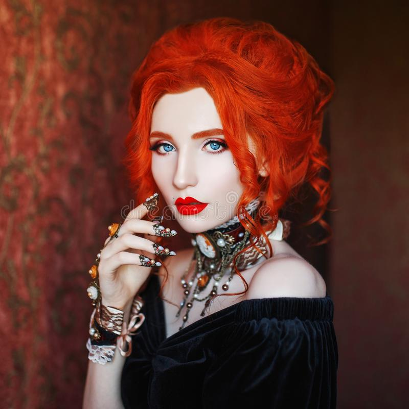 Sharp claws. Dark halloween attire. Sorceress woman is vampire with pale skin and red hair in black dress and necklace on neck. royalty free stock photo