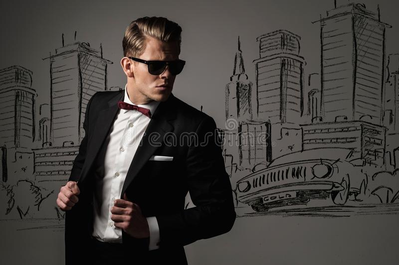 Sharp dressed man in black suit against city stock image