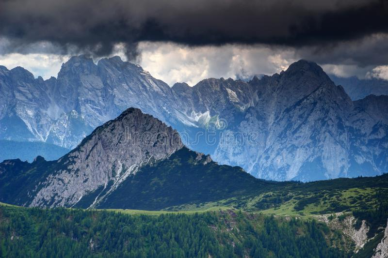 Sharp edged peaks under threatening dark clouds in Carnic Alps. Sharp edged peaks and rock faces of Main Ridge and Monte Brentoni Group of Alpi Carniche under royalty free stock photography