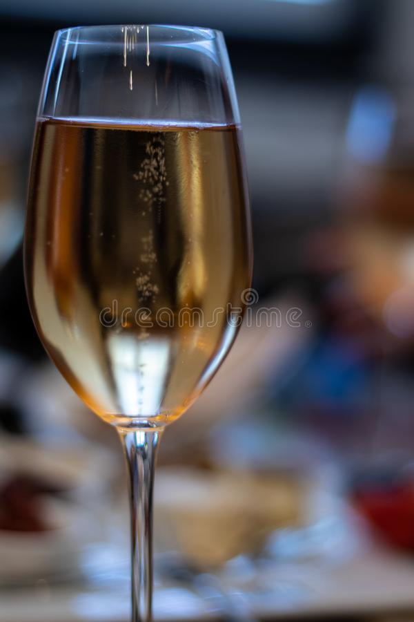 Sharp focus on single wine glass with white wine bubbling. In crystal glass royalty free stock photo