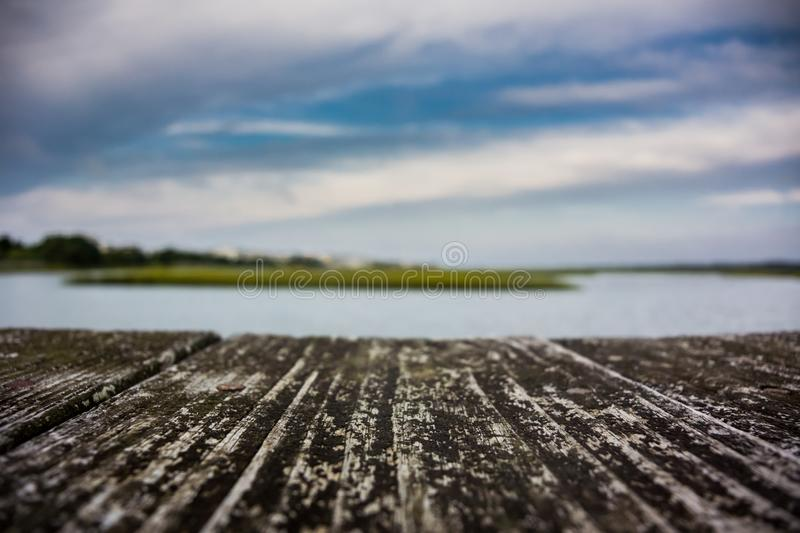 Inlet over Wooden Boardwalk. A sharp focus on a wooden boardwalk in front of a blurred marsh inlet stock photos