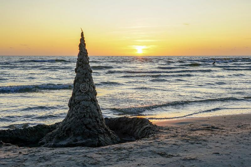A sharp, high sand castle on the sandy seashore against a sunset background stock images