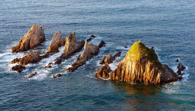 Sharp islets. Asturias, Spain. Sharp islets near Gueirua beach (Asturias, Spain). Evening Atlantic ocean landscape stock image
