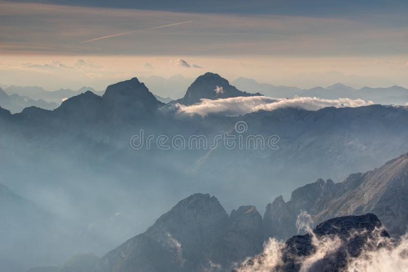 Sharp Jalovec and Mangart peaks tower above hazy Trenta valley. Jalovec and Mangart peaks towering above hazy Trenta valley and serrated rocky crests in glowing stock photography