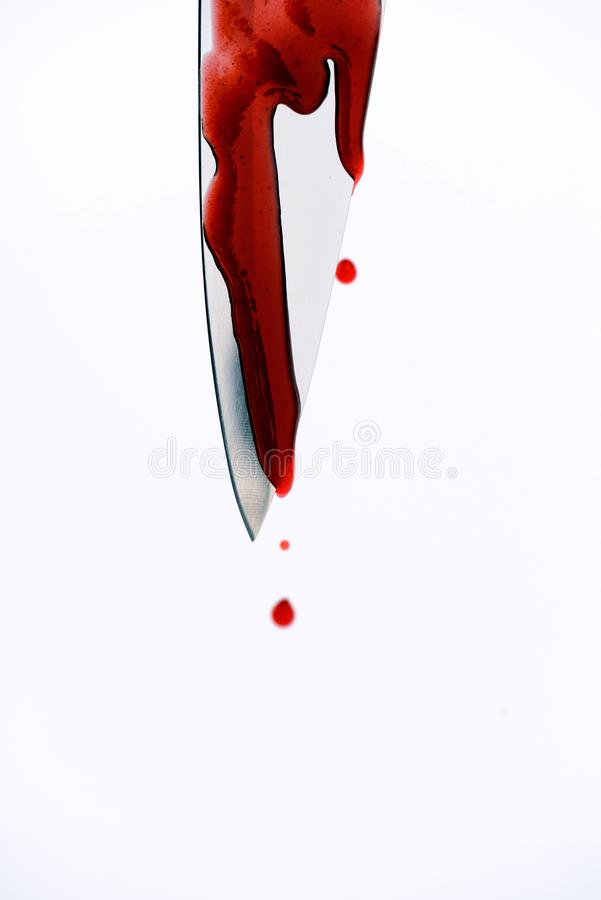 Sharp Murder Knife Weapon with Blood Dripping Droplets. Sharp metal kitchen knife with blood dripping from its edge in a vertical shot royalty free stock photos