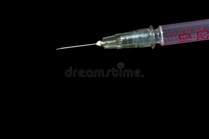 Syringe, injection needle on black background. Sharp needle of syringe, Insulin injection on black background stock photos