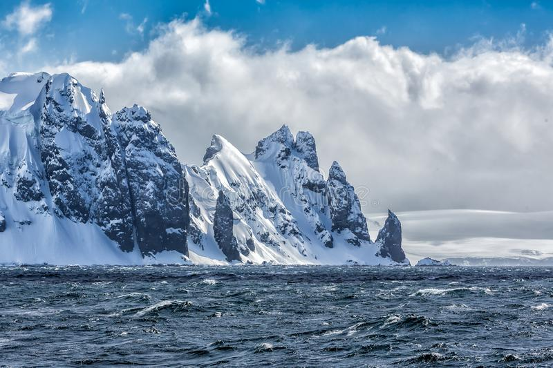 Sharp new mountain peaks covered in snow near Concession Bay, Antarctica. South pole royalty free stock image