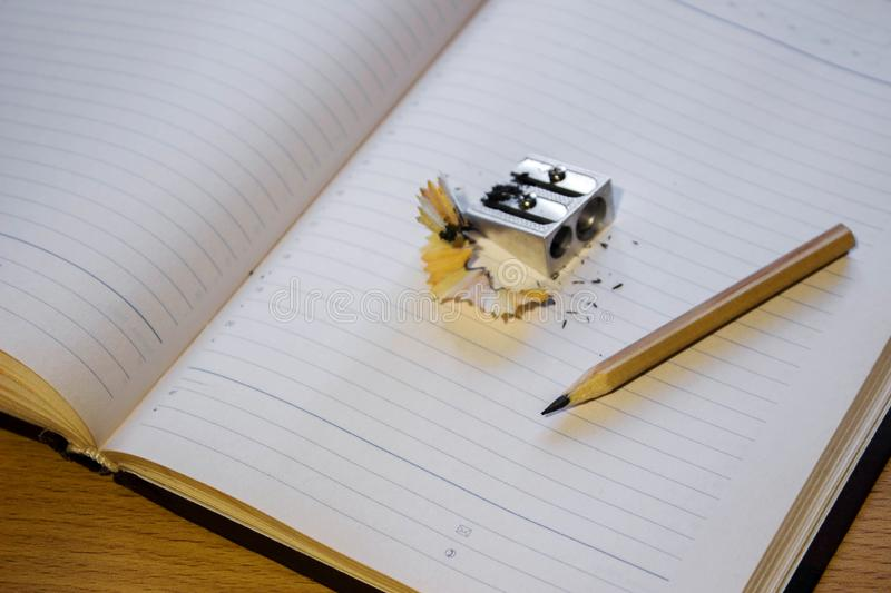A sharp pencil with a sharpener on the diary or notebook royalty free stock photo