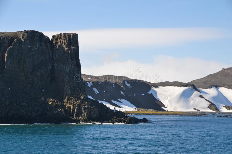 Brown cliff edge in Antarctica. A sharp and rectangular cliff edge stands out from the snowy Antarctic landscape royalty free stock photo