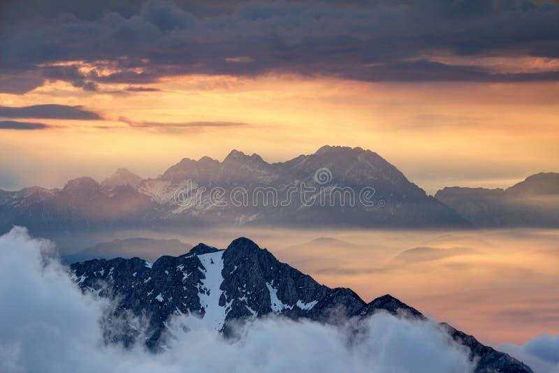 Sharp ridges of Slovenian Alps rise above orange sea of clouds royalty free stock image
