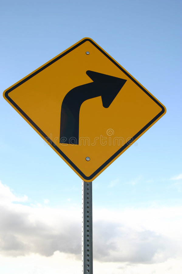 Sharp Right Turn Sign. This is a yellow road sign with a black arrow indicating there is a sharp turn to the right ahead. The sign is clean and appears to be new royalty free stock photography