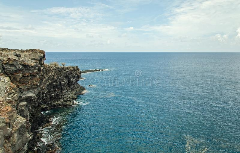 Sharp rock and clean empty blue sea and clouds royalty free stock photo