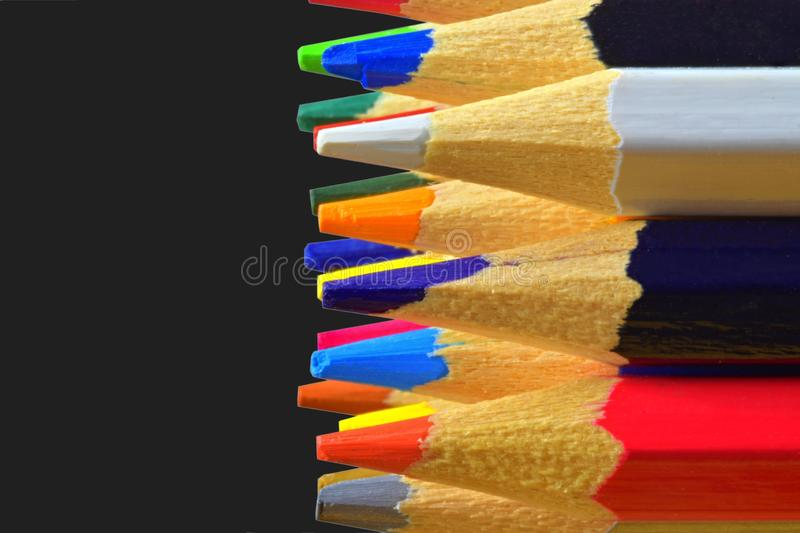 The sharp tips of the pencils. Bright colored pencils. Colored pencils on black background with selective focus. Write royalty free stock photo
