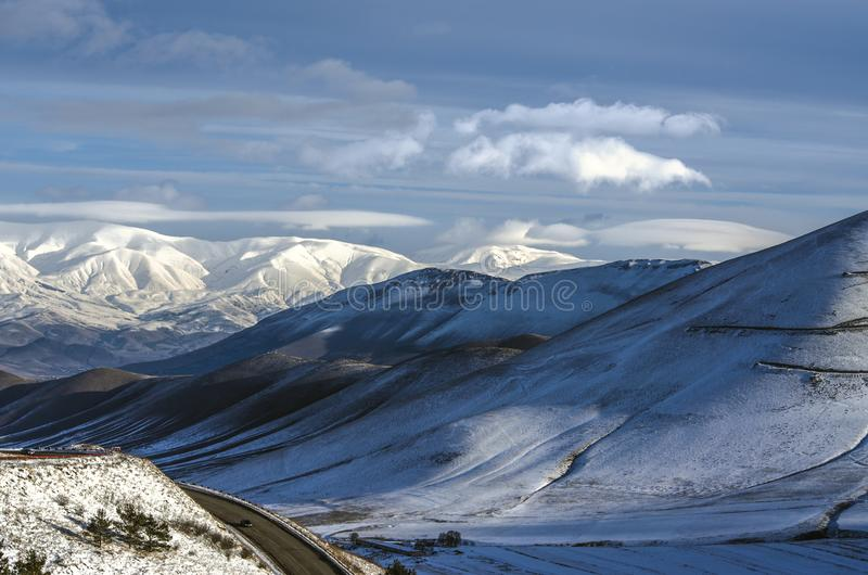 The sharp turns on the way to the city of Spitak and the first rays of the winter sun, scattering the fog in the mountains of Arag stock image