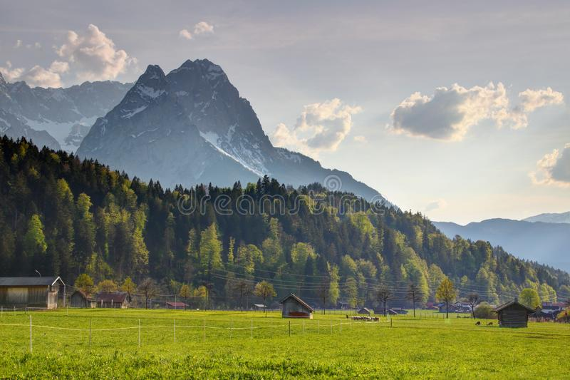 Sharp Waxenstein and Zugspitze peaks tower above small barns stock photos