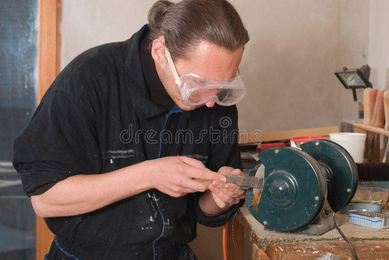 The sharpen. Young carpenter sharpen a chisel on grinding machine, sparks fly royalty free stock photo