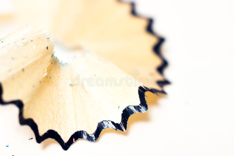 Sharpened blue pencil sharpener with shavings on a white background stock photography
