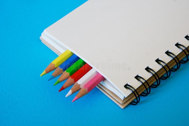Sharpened coloreó los lápices miente así como una libreta en blanco en un fondo azul imagen de archivo libre de regalías