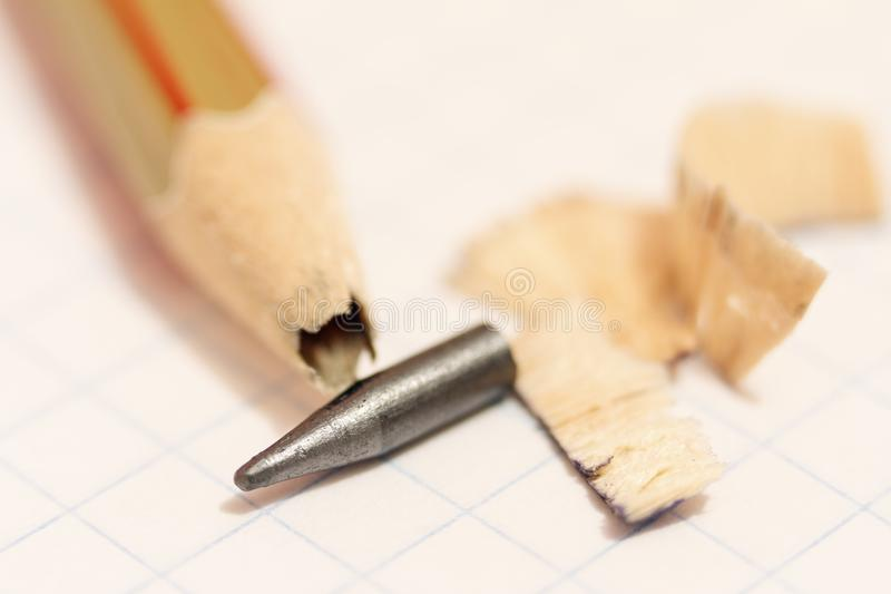 Sharpened pencil with a broken tip over a blank sheet of paper.  stock image