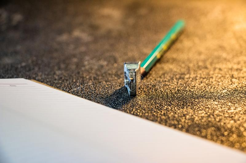 Sharpened pencil lies on a notebook, top view. Black background. Pencil planer. Close-up royalty free stock image
