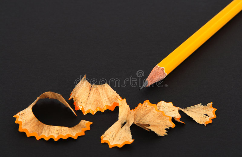 Sharpened pencil and wooden shavings. On dark background royalty free stock photo