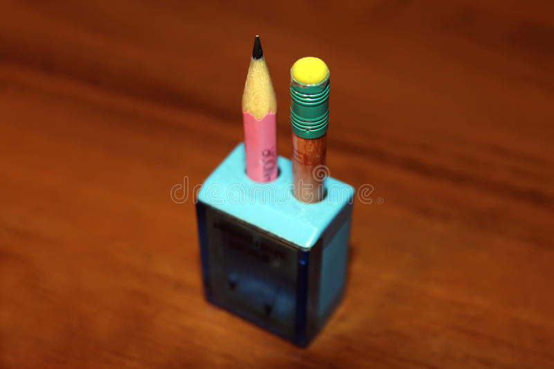 Sharpened pencils in a blue pencil sharpener on brown table royalty free stock photo