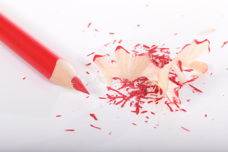 Sharpened red pencil with shavings. On white background, viewed from above royalty free stock photos