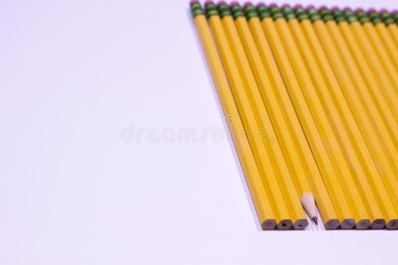 Angle of sharpened pencil in line of unsharpened pencils on white background with copy space royalty free stock image