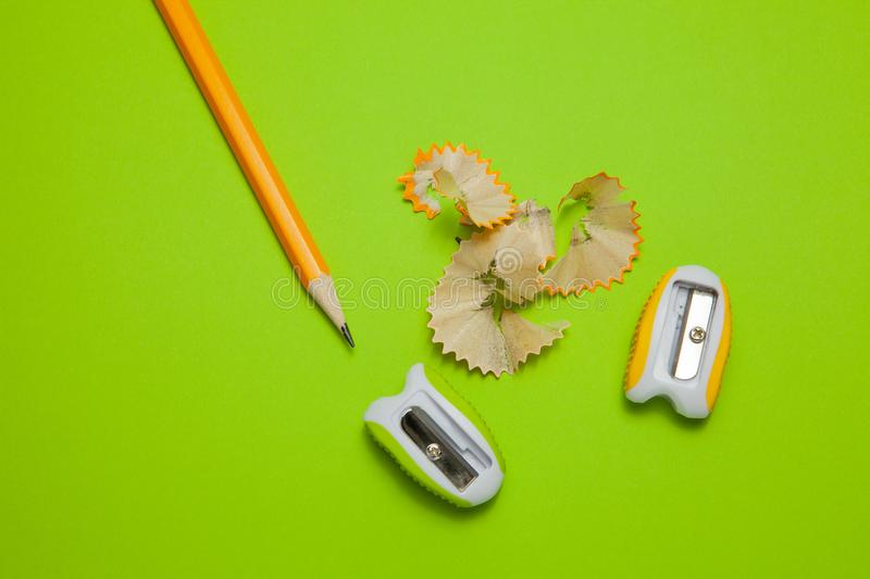 Sharpeners and pencil on green background, top view royalty free stock photography