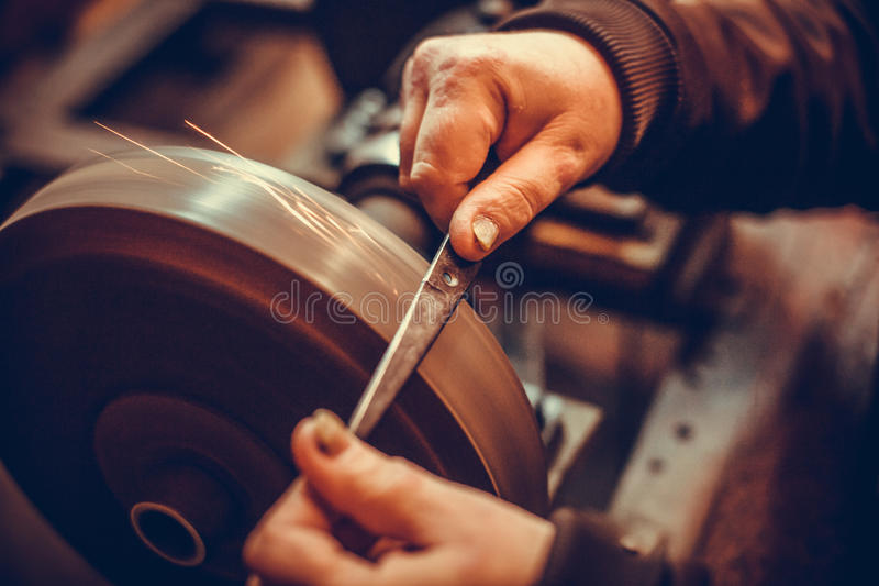 Sharpening scissors detail. Close up shot of a man`s hands sharpening a scissors stock images