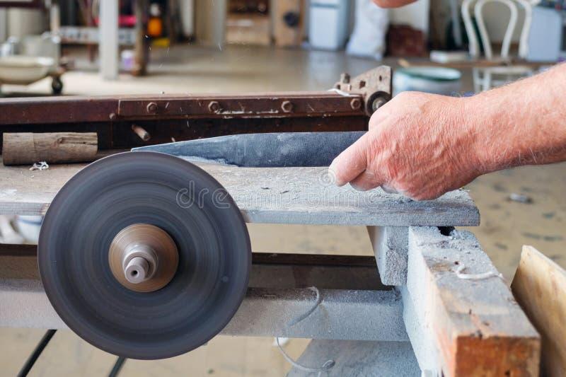 sharpering在磨石的刀子工作者的手 免版税图库摄影