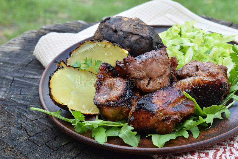 Shashlik with baked potatoes and cabbage salad on clay plate. Marinated meat cooked over charcoal on barbecue grill. Shish kebab. stock photography