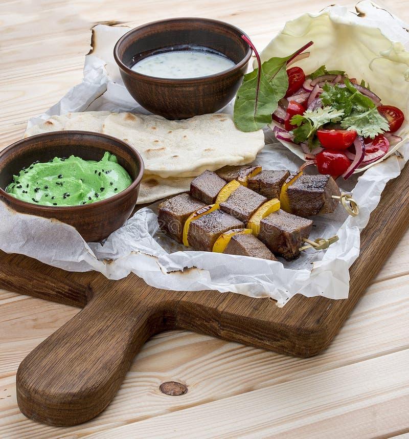 Shashlik del vitello con il hummus verde e salsa di Dzadziki con rafano immagine stock