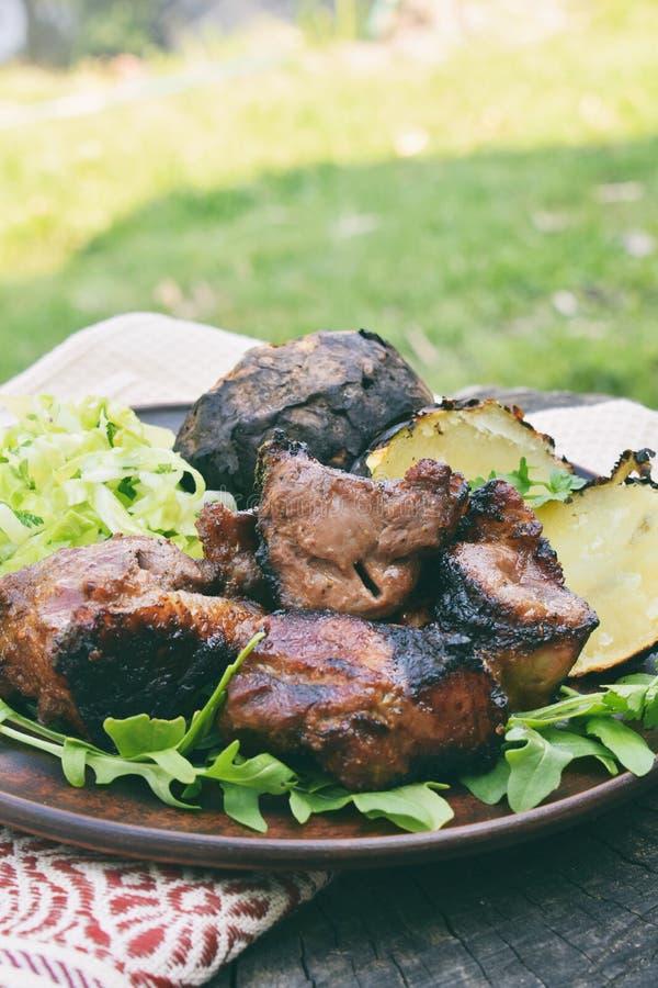 Shashlik mit Ofenkartoffeln und Kohlsalat auf Lehmplatte Mariniertes Fleisch kochte ?ber Holzkohle auf Grillgrill Bratenfleisch a stockfotografie