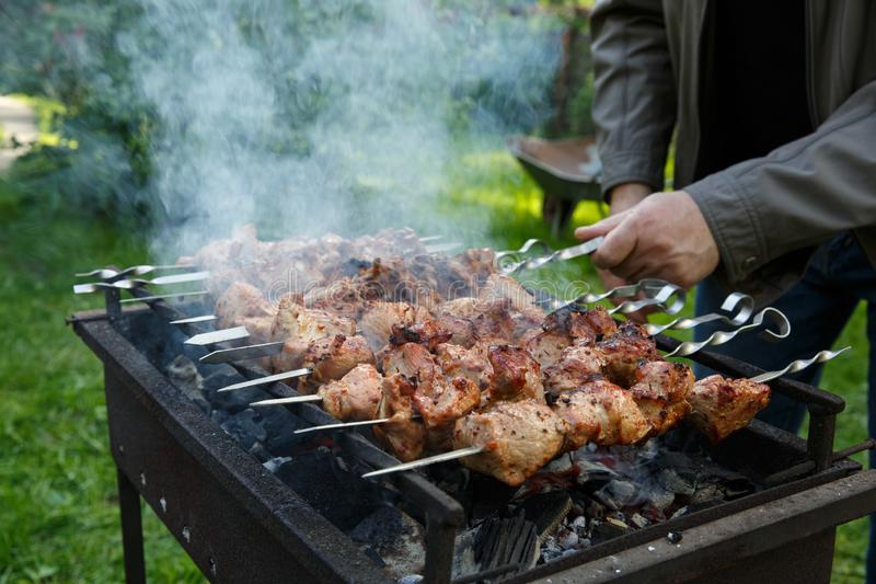 Shashlik or shashlyk preparing on a barbecue grill over charcoal. Grilled cubes of pork meat on metal skewer. Outdoor.  royalty free stock image