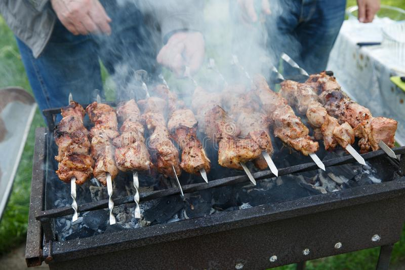 Shashlik or shashlyk preparing on a barbecue grill over charcoal. Grilled cubes of pork meat on metal skewer. Outdoor.  royalty free stock photo