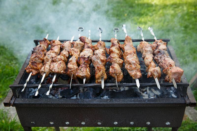 Shashlik or shashlyk preparing on a barbecue grill over charcoal. Grilled cubes of pork meat on metal skewer. Outdoor.  stock image