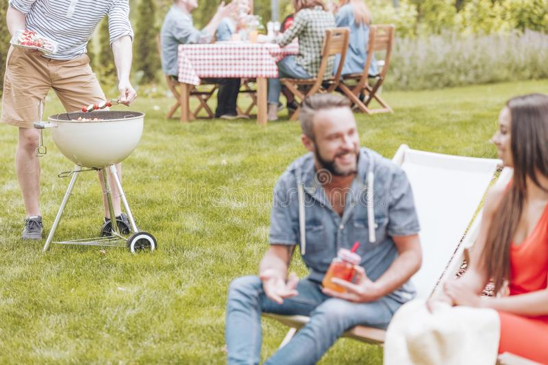 Shashliks being put on a grill by a man during a BBQ party. Blur. Shashliks being put on a grill by a men during a BBQ party. Blurred foreground with a women and royalty free stock image