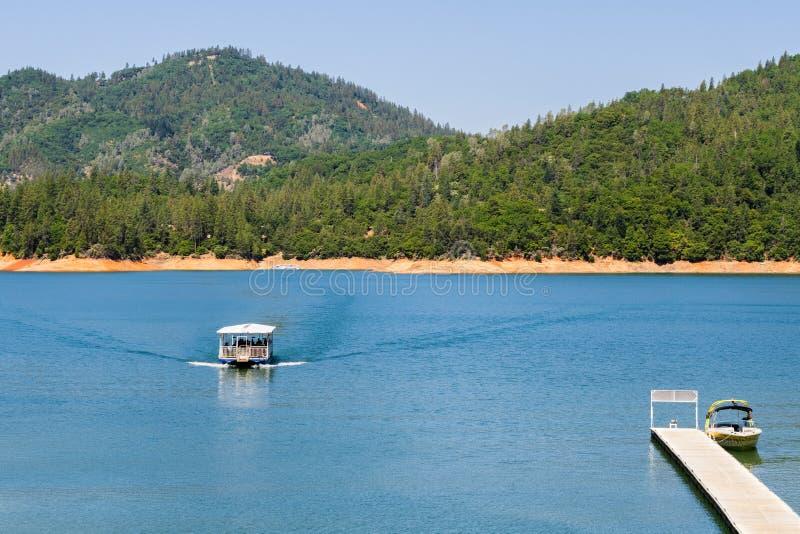 Shasta jezioro, McCloud ręki Rzeczny krajobraz na pogodnym letnim dniu z statkiem zbliża się linię brzegową, Północny Kalifornia zdjęcie stock