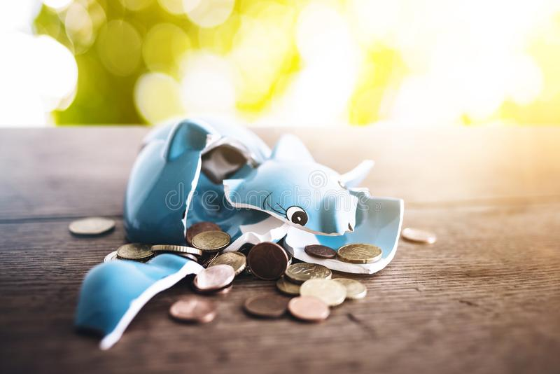 Shattered broken piggy bank with coins on rustic wooden table finance concept. Closeup of shattered broken piggy bank with coins on rustic wooden table finance stock image
